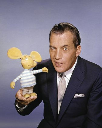 "Ed Sullivan, host of ""The Ed Sullivan Show,"" CBS' long-running (1948-1971), top-rated Sunday night variety show. Ed is shown with the little lovable Italian mouse puppet, Topo Gigio, that made more than fifty Sullivan appearances. On the show, Topo Gigio greeted Ed with a sugary ""Hello Eddie!"" and ended his weekly visits by crooning to the host, ""Eddie, Keesa me goo'night!"""