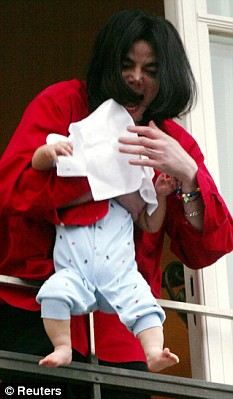 Michael Jackson is shown dangling his newborn baby, Prince Michael Jackson II (also known as Blanket) from a Berlin hotel balcony