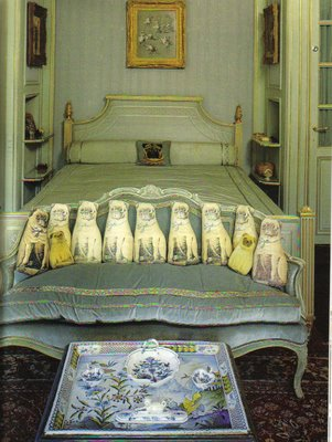 "In 1997, Sotheby's auctioned off the contents of the Paris home of the Duke and Duchess of Windsor. Included in their possessions were these pug pillows arranged at the foot of the Duchess' bed. Although Wallis, the Duchess, was fastidious about cleanliness, she allowed the pugs to sleep in the bed with her. """"Paper money for the Duchess was either ordered new and crisp from a bank or wash cleaned and ironed by the housemaids; coins were always washed. Each evening, just before dinner was served, two maids could be found carrying bedsheets through the halls by their corners; the bed linens, having just been ironed, were destined for the rooms of the Duke and Duchess. Wallis could not stand wrinkles in her bed….Once the bed was made, a plastic sheet was spred atop the satin eiderdown so that the pugs could climb onto the bed with Wallis; there she would feed them the hand-baked dog biscuits prepared fresh each day by her chef. Usually the pugs slept on the bed with her, although the Duke's favorite might disappear through the boudoir to his own spot at the foot of his master's bed."" The Duchess of Windsor: The Uncommon Life of Wallis Simpson by Greg King"
