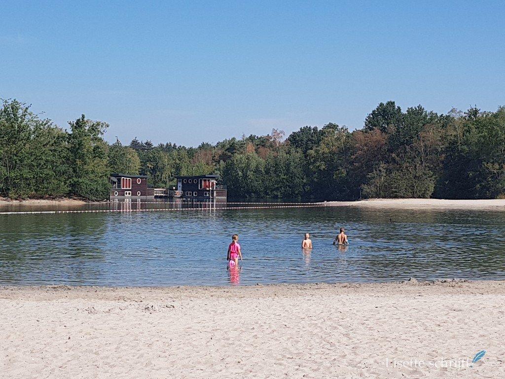 Drie kinderen in het meer van de kempervennen met woonboten op de achtergrond.