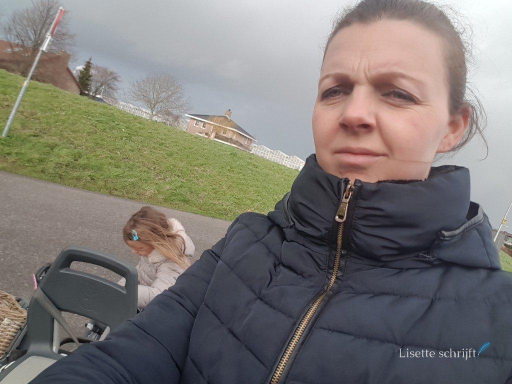 moeder op de fiets met dochter tijdens zware bewolking