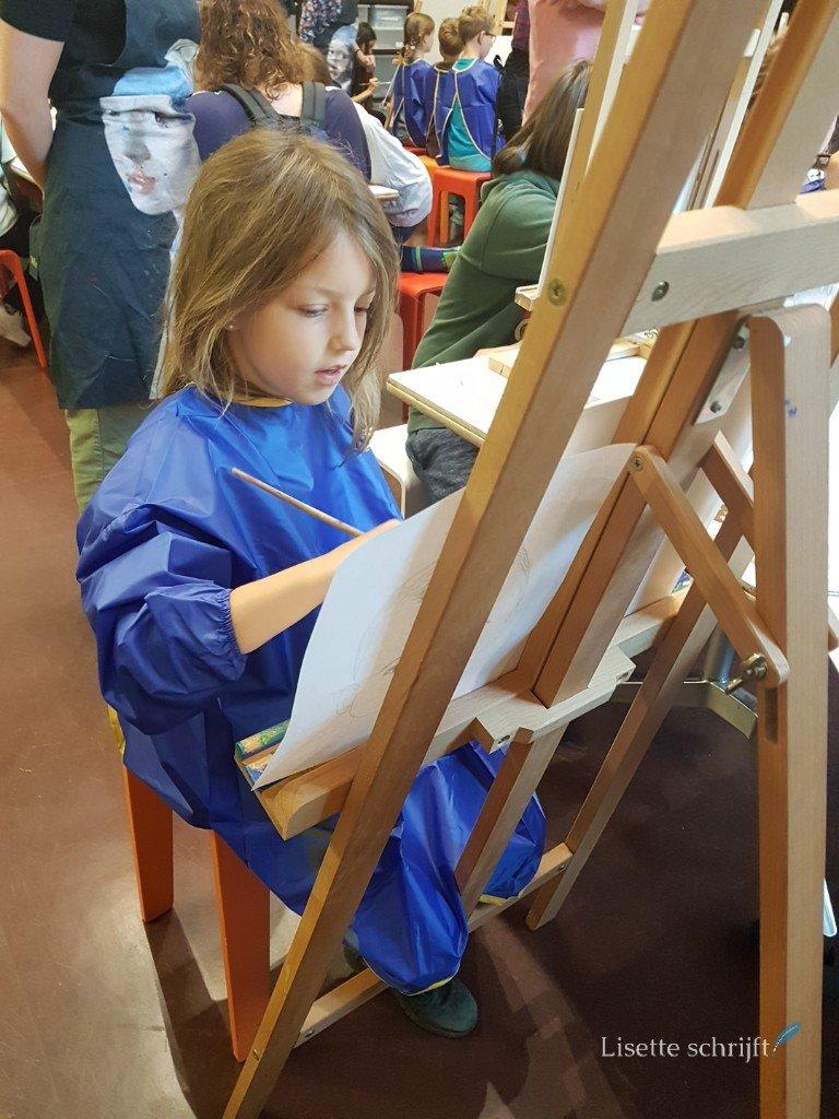 meisje schildert achter een ezel