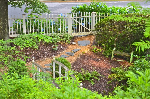 The hosta and ferns are filling in by the gate