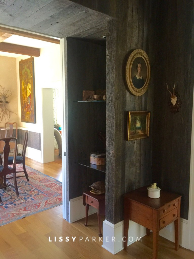 Antique barn wood lines the hall and recessed cabinets