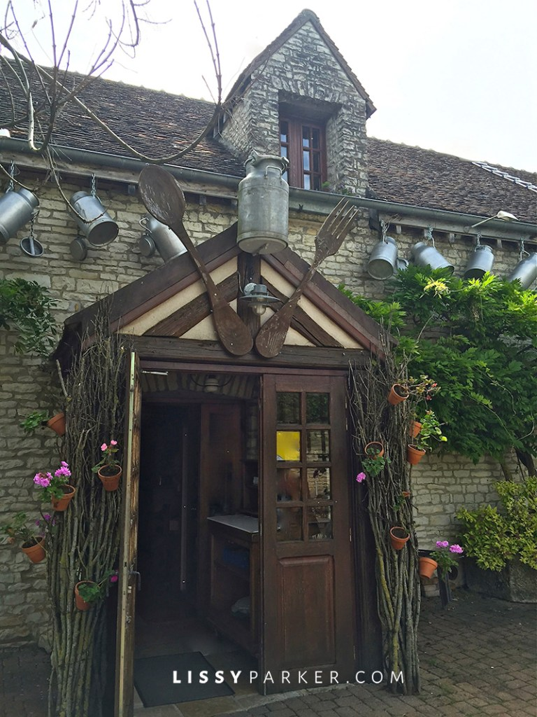 Warm Friendly France-restaurant entrance with milk pails and large fork and spoon
