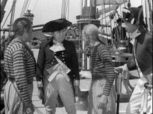 Charles Laughton as Captain Bligh standing on the deck of the Bounty