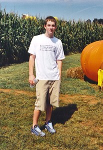 Clint Reagan standing in a corn maze with a pumpkin in the background