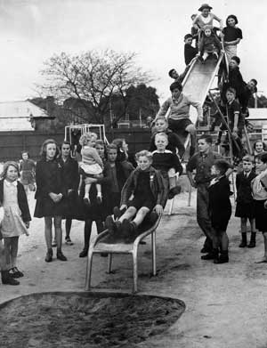 Children playing on a metal slippery dip.
