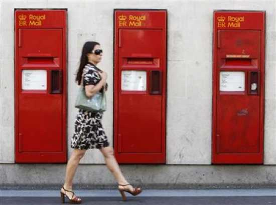 11960-A-Woman-Passesrow-Of-Royal-Mail-Post
