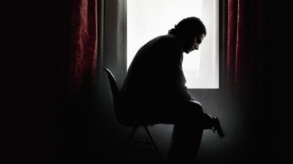 Man sits in shadows with gun