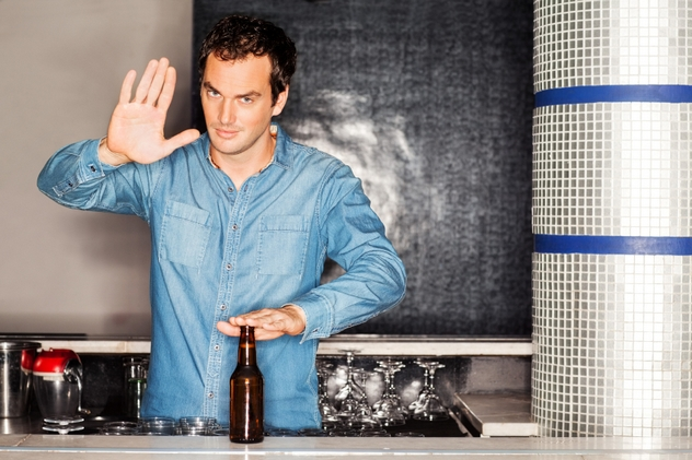 Bartender With Beer Bottle Gesturing Stop Sigh At Counter