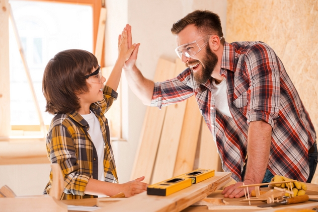 We did it! Cheerful young male carpenter and his son giving high-five to each other while working in workshop