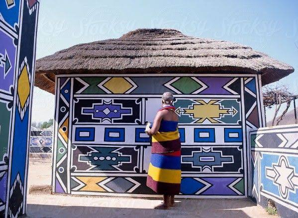 An Ndebele woman painting her front walls