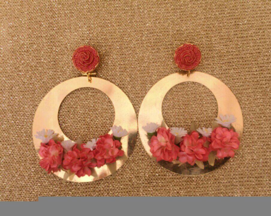 Pendientes en forma de aros dorados con apliques de flores secas en tonos coral.
