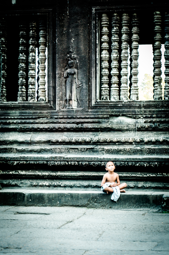 Boy sitting at Angkor Wat
