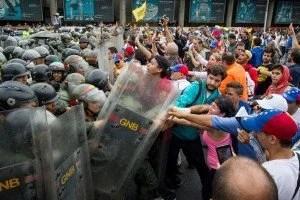 CAR23. CARACAS (VENEZUELA), 11/05/2016.- Simpatizantes opositores chocan con miembros de las Fuerzas Armadas Bolivarianas de Venezuela (FANB) durante una manifestación hoy, miércoles 11 de mayo de 2016, en la autopista Francisco Fajardo de Caracas (Venezuela). La policía militarizada de Venezuela y la estatal Policía Nacional Bolivariana (PNB) impidieron el paso de la marcha a la que convocó hoy la oposición del país hasta la sede del Poder Electoral para pedir celeridad en la activación de un referendo para revocar al presidente, Nicolás Maduro. EFE/Miguel Gutiérrez