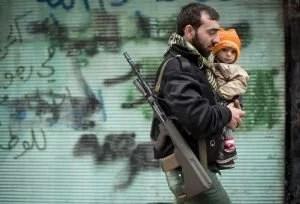 Un rebelde sirio carga un bebé entre las ruinas de Alepo