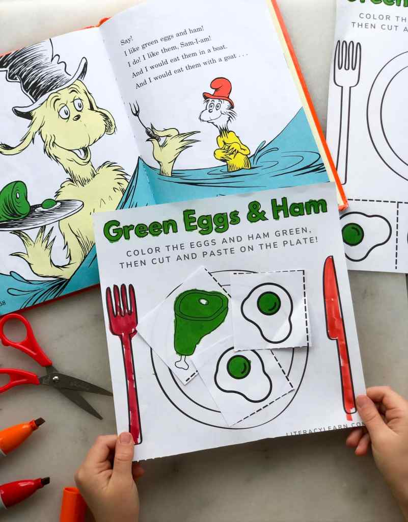 Two child's hands holding the finished worksheet near an open copy of Green Eggs and Ham.