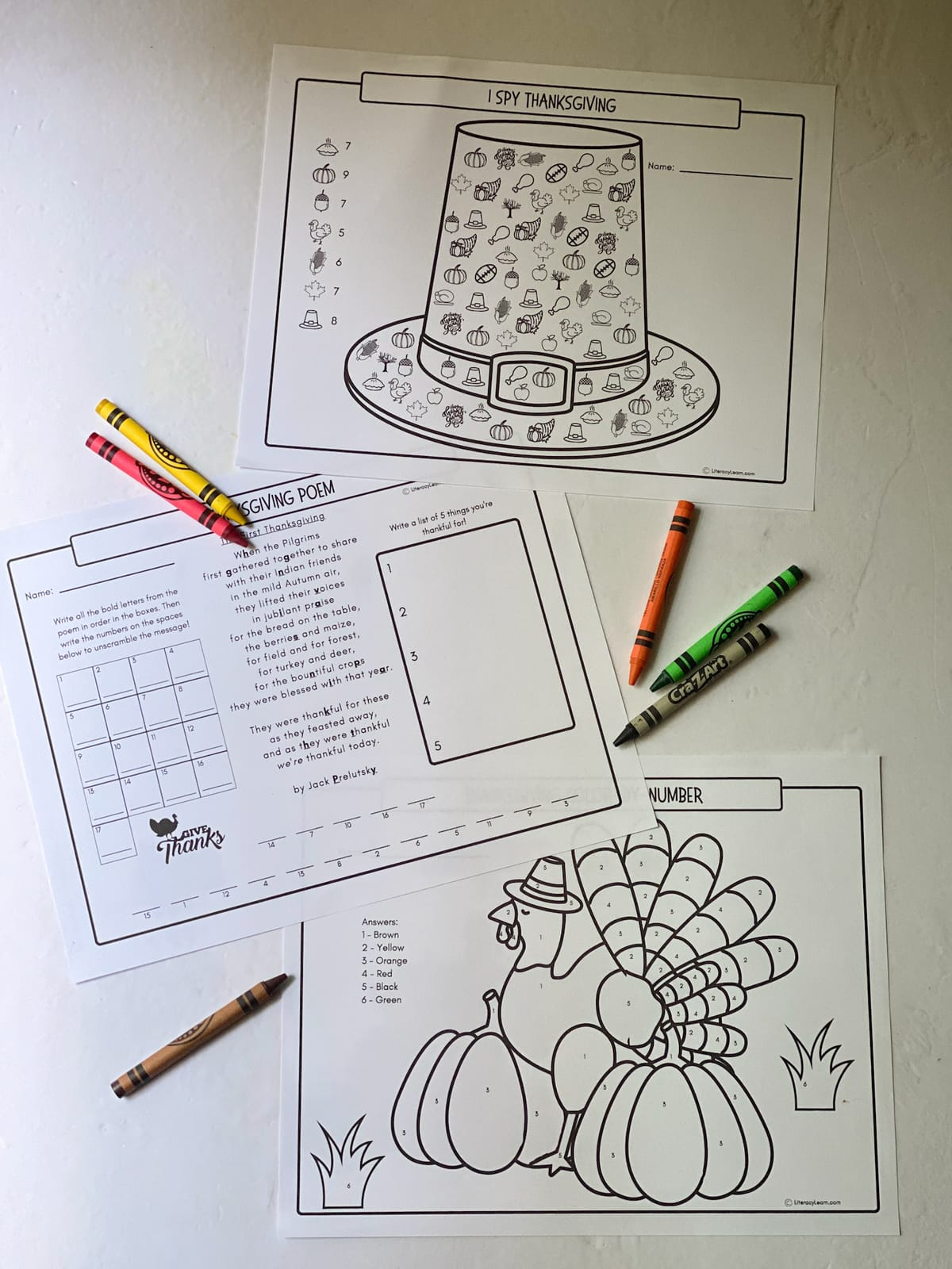 The three printed placemats on a white background with crayons.