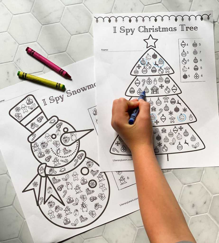 A child's hand holding a crayon, circling the I Spy items on the worksheets.