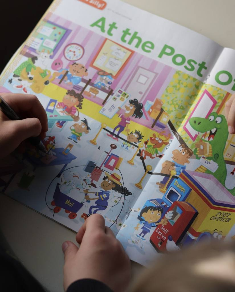 Child's hands searching a puzzle book.