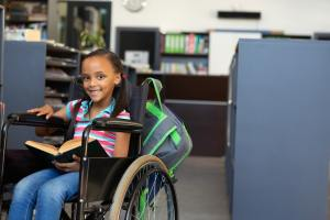 Front view of a happy disabled mixed-race schoolgirl reading a book in the classroom at school