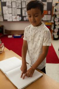 Front view of blind mixed-race schoolboy reading a braille book in classroom at elementary school