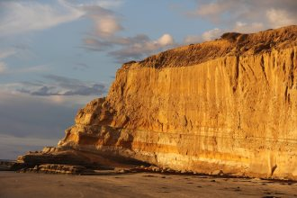 A setting sun lights up a sea cliff at Torrey Pines State Beach. Credit: S. Johnson