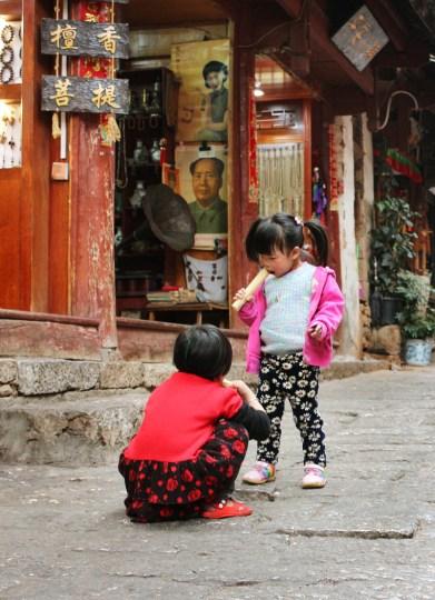 Zwei Mädchen knabbern Zuckerrohr in Lijiang Old Town
