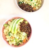 Quinoa bowls with lots of steamed veggies mixed through, avocado and lentils on top with a tahini and lemon dressing