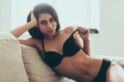 Feeling playful. Beautiful young mixed race woman in black lingerie looking at camera and taking off her bra while sitting on couch at home