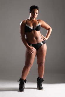 BBW big beautiful african american woman showing off plus size curvy figure wearing sexy black lingerie and boots.