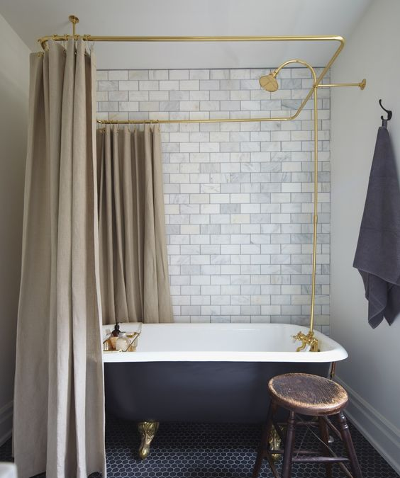 Marble subway tile behind claw foot tub with black painted surface
