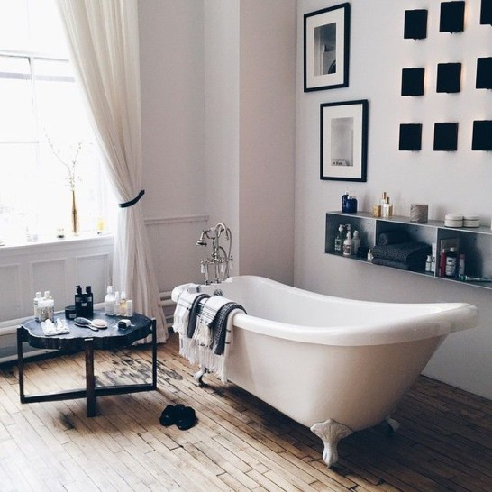 claw foot tub on worn wood floor with metal product shelf on wall