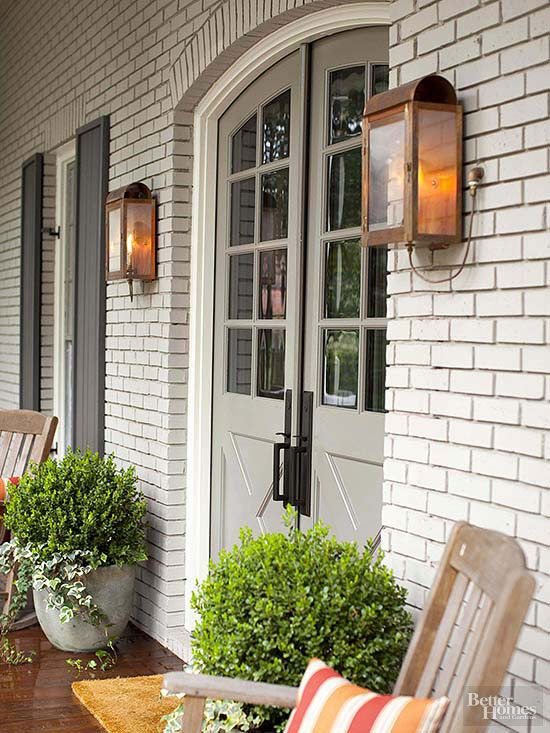 White Brick Front Porch, Gas Lanterns, Boxwood Planters At Entry, Plank Window Shutters, Double Door Entry, Rockers On The Porch