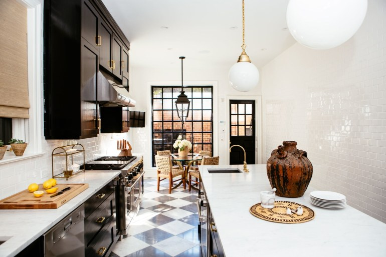 Black and White Checkerboard Floor, Black Cabinets with Brass Hardware, Rattan Furniture
