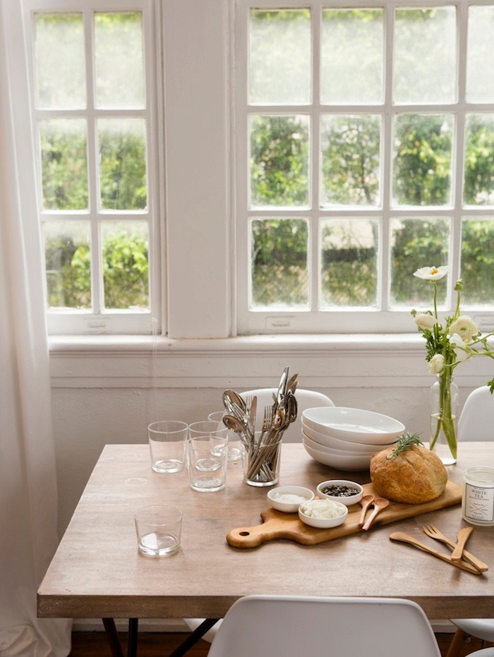 Table with glasses, soup bowls, spoons, wooded cutting board with bread