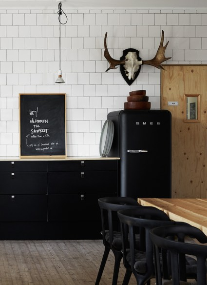 black smeg refrigerator , moose head art, chalkboard in kitchen, black cabinets, butcher block top