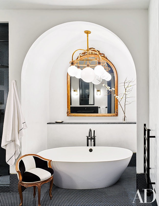 Architectural Digest Tub In An Alcove, Black Penny Floor Tile, Vessel Soaking Tub, Gold Mirror and Statement Light Fixture, Black and White Stripe Vanity Chair