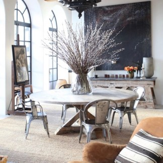transitional dining room with large washed wood round dining table, metal chairs, large glass vase with pussy willows in center of table, wood beamed ceiling, natural woven area rug and rusty colored suede easy chair with black and white striped pillow