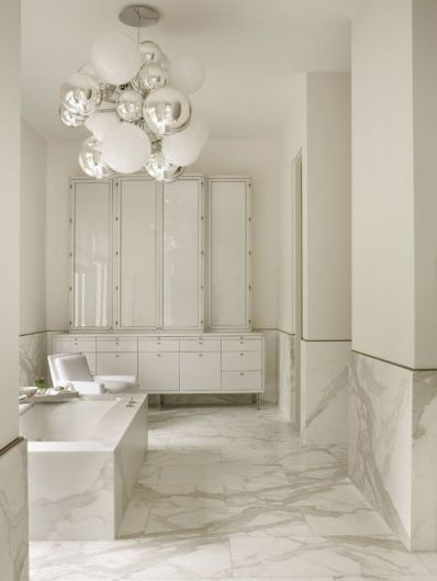 house beautiful marble bathroom with shades of white paint, chrome and white round globe statement chandelier , marble tub, white glass tall storage cabinets