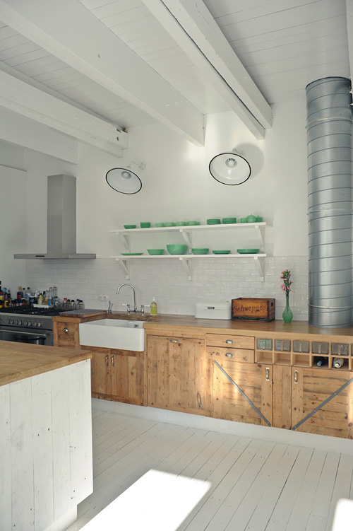 Warehouse style kitchen with painted white beams, open shelving with green glass dishes, painted wood floors and school house lighting. - via remodelista