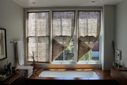 soaking tub in front of 3 windows with burlap shades, wood deck on around tub, chrome faucets- via remodelista