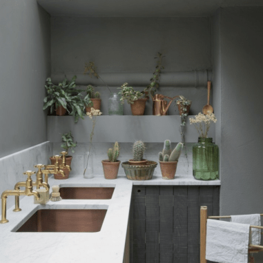 Small kitchenette with white marble tops, copper sinks, brass taps, succulents in clay containers on counter with large green glass jar with cut white flowers, clothes drying rack nearby with white towels on it, soft gray walls and dark gray base cabinets