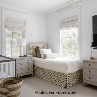 white walled nursery with white crib and upholstered twin bed, black background white jellyfish art, woven basket next to crib and rattan box on painted dresser, linen roman shades at windows