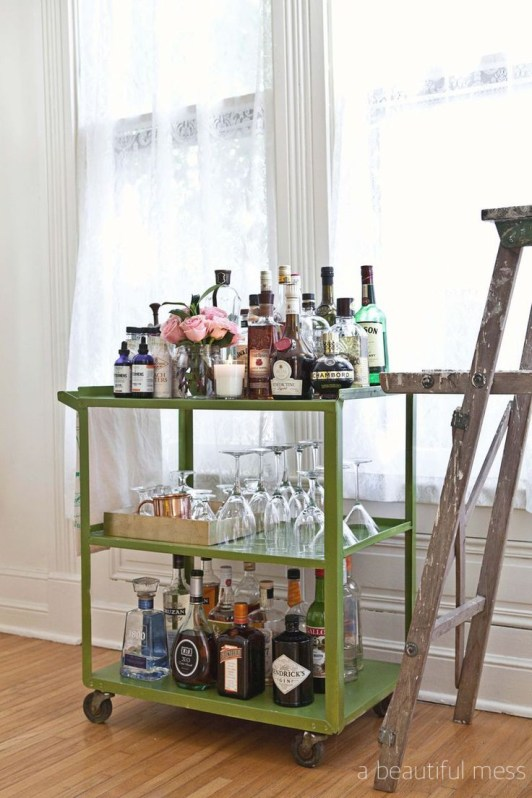 beautifulness lime green painted bar cart with colorful bottles, pink roses and wine glasses