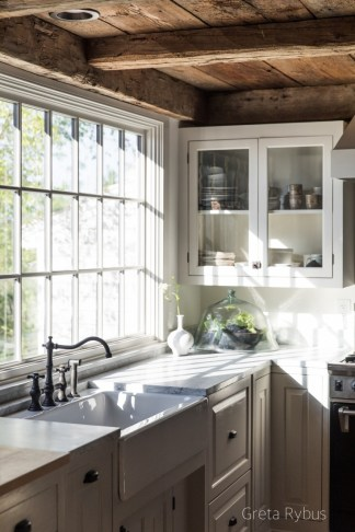 Greta Rybus Kitchen With Rustic Wood Beam Ceiling, Farmhouse Sink, Glass Door Cabinet and Marble Counter Tops