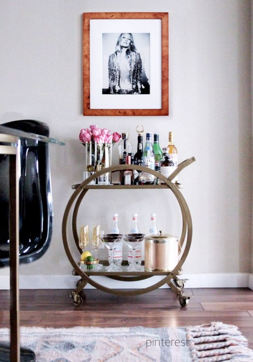 pinterest round circle bar cart with bottled water, copper ice bucket and pink roses with photo of kate moss overhead
