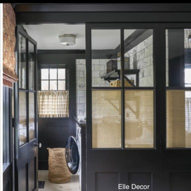 Black framed laundry room with glass panels in door and wall to see thru to carrara white block walls, wnwashed wood pine floor, woven tan shades at a few of the windows, two handled woven laundry basket on floor in front of dryer, black open shelves on wall with laundry products