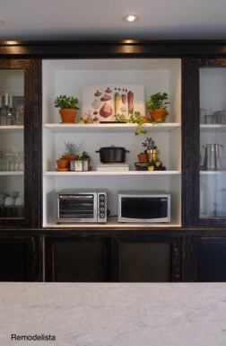- freestanding black 3 section tall cabinet with closed doors on bottom and open bookcase shelves on upper third section, interior of bookcase painted white as contrast to black frame, used for kitchen counter oven, microwave and cooking item storage on display